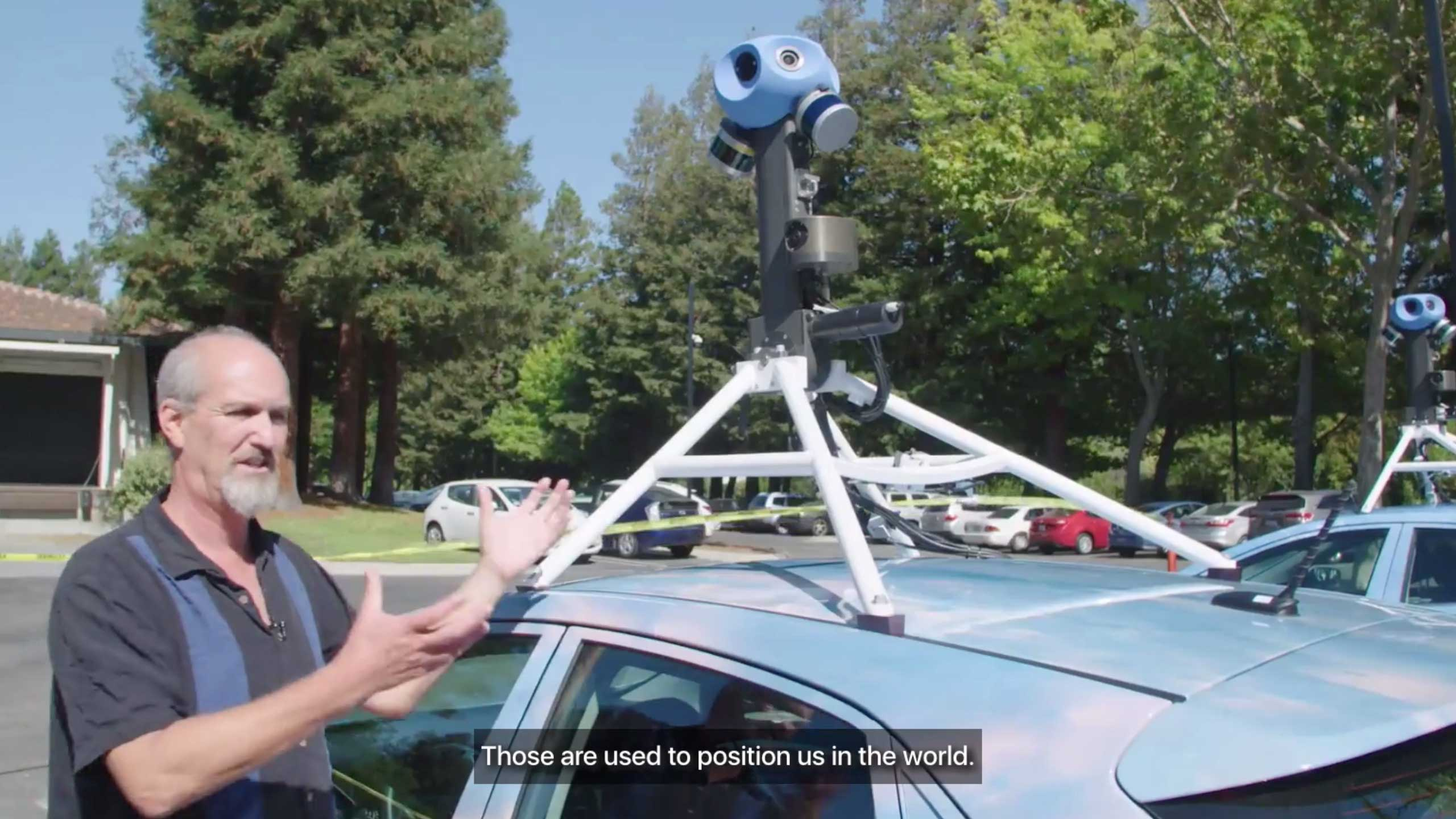 """A white man stands beside a car with a camera mounted on its roof. A visible caption says """"Those are used to position us in the world."""""""